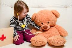 Gullig flicka som spelar doktorn med den flotta leksakbjörnen Fotografering för Bildbyråer