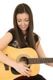 Gullig flicka som spelar hennes akustiska gitarr som ner ser Royaltyfria Bilder