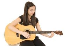 Gullig flicka som spelar hennes akustiska gitarr som ner sitter Arkivfoton