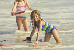 Gullig flicka som spelar i havet på ett boogiebräde Royaltyfria Foton