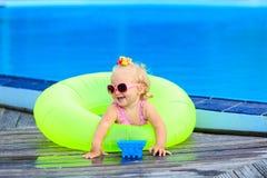 Gullig flicka som spelar i simbassäng på stranden Arkivfoto