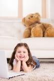 Gullig flicka som spelar lekar på datoren Fotografering för Bildbyråer