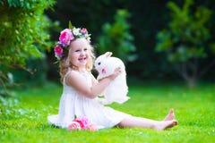 Gullig flicka som spelar med den verkliga kaninen Arkivbild