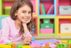 Gullig flicka som spelar med plast- kvarter Arkivbilder