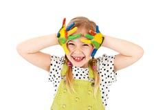 Gullig flicka som spelar med vattenfärger, isolerad studiostående Arkivfoto