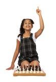 Gullig flicka som spelar schack på vit Arkivbilder