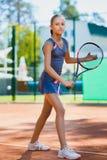 Gullig flicka som spelar tennis och i rätten poserar inomhus arkivbilder