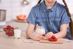 Gullig flicka som tillfogar jordgubben till yoghurten i krus royaltyfri foto