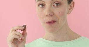 Gullig flicka som tuggar choklad stock video