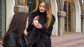 Gullig flicka som två talar och dricker kaffe på gatan arkivfilmer