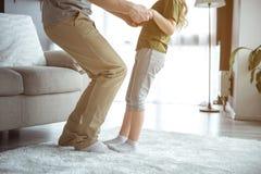 Gullig flicka som tycker om dans med pappa i rum fotografering för bildbyråer