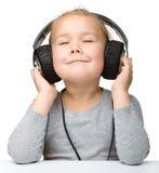 Gullig flicka som tycker om musik genom att använda hörlurar Royaltyfri Foto