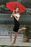 gullig flicka som under hoppar det röda tonårs- paraplyet Royaltyfria Foton