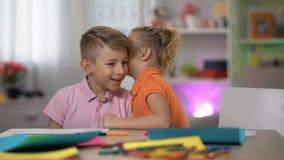 Gullig flicka som viskar det hemliga broderörat som tillsammans skrattar, skvallra för barndom stock video