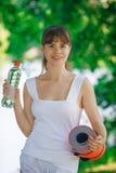 Gullig flicka utomhus med en sportfilt och en flaska av vatten Royaltyfri Foto