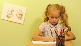 Gullig flickaattraktionbild Kulöra tryck av barn` s gömma i handflatan Flickan sitter på en tabell och målar en bild stock video