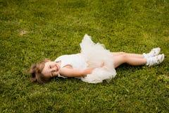 gullig flickagreen little liggande äng royaltyfri fotografi