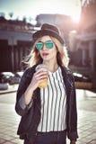 Gullig flickahåll en fruktsaft i staden i solglasögon med hatten Fotografering för Bildbyråer