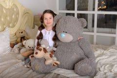 Gullig flickakram Big Bear på säng arkivfoton