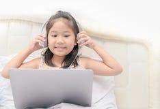 Gullig flickalekbärbar dator och lyssnande musik royaltyfria bilder