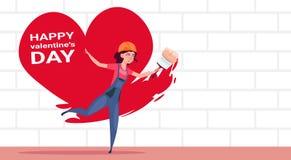 Gullig flickamålare Paint Red Heart Shape på det vita begreppet för garnering för dag för valentin för tegelstenvägg lyckliga Arkivbild