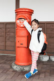 Gullig flickaturist som överförs bokstav till postboxen Royaltyfria Bilder