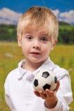 gullig fotbollholding för pojke utomhus royaltyfri bild