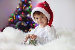Gullig förtjusande pojke som tycker om hans godis på jultid Arkivbild