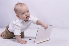Gullig fundersam pojke i den vita skjortan som spelar med en minnestavla Den roliga begynnande pojken med bärbara datorn ser som  Royaltyfri Bild