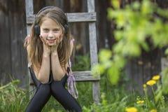 Gullig girlie tycker om musik med hörlurar royaltyfri fotografi