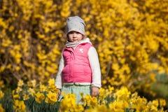 Gullig girlon ett bakgrundsfält med gula blommor, den lyckliga gulliga och härliga ungen som har gyckel med gula blommor i vår pa royaltyfri foto