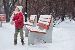Gullig gladlynt barnflickadanande kastar snöboll i den snöig vintern parkerar Arkivbilder