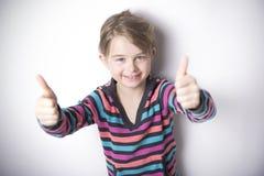 Gullig gladlynt liten flickastående, på grå bakgrund royaltyfria foton