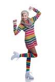 Gullig gladlynt tonårs- flicka som bär den färgrika randiga tröjan, halsduken, handskar, hatten och isolerade vitkängor Mode och  Arkivfoto