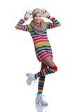 Gullig gladlynt tonårs- flicka som bär den färgrika randiga tröjan, halsduken, handskar, hatten och isolerade vitkängor Mode och  Royaltyfria Foton