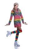 Gullig gladlynt tonårs- flicka som bär den färgrika randiga tröjan, halsduken, handskar, hatten och isolerade vitkängor Mode och  Royaltyfri Bild