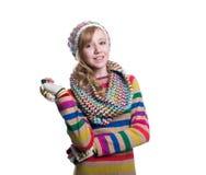 Gullig gladlynt tonårs- flicka som bär den färgrika randiga tröjan, halsduken, handskar och hatten som isoleras på vit bakgrund M Royaltyfria Bilder