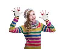 Gullig gladlynt tonårs- flicka som bär den färgrika randiga tröjan, halsduken, handskar och hatten som isoleras på vit bakgrund M Royaltyfri Bild