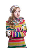 Gullig gladlynt tonårs- flicka som bär den färgrika randiga tröjan, halsduken, handskar och hatten som isoleras på vit bakgrund M Arkivfoton