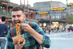 Gullig grabb som utomhus äter asiatiska nudlar royaltyfri foto