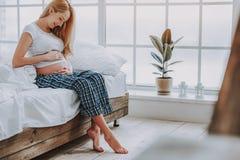 Gullig gravid kvinna som ler till hennes buk i hemtrevligt sovrum arkivbild