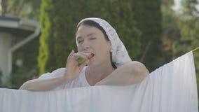 Gullig hög kvinna för stående med sjalen på hennes huvud som äter paprika som ser kameran som ler över klädstrecket stock video