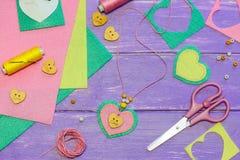 Gullig halsband för filthjärtahänge Saxen tråden, filt täcker och lappar, knappar, pappers- mall på en trätabell Arkivbilder