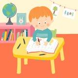 Gullig handstil för skolapojke på skrivbordet i klassrum Royaltyfria Foton