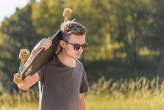 Gullig Hipster med Longboard Arkivfoto