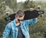Gullig Hipster med Longboard Arkivbild