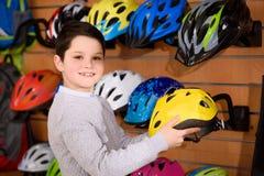 gullig hjälm för pysinnehavcykel och le på kameran i cykel arkivbilder