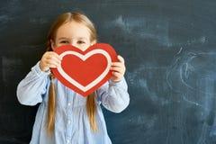 Gullig hjärta för liten flickainnehavpapper fotografering för bildbyråer