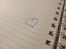 Gullig hjärta som dras i anteckningsbok Arkivfoto