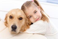 gullig hund som little omfamnar flickan Arkivbilder